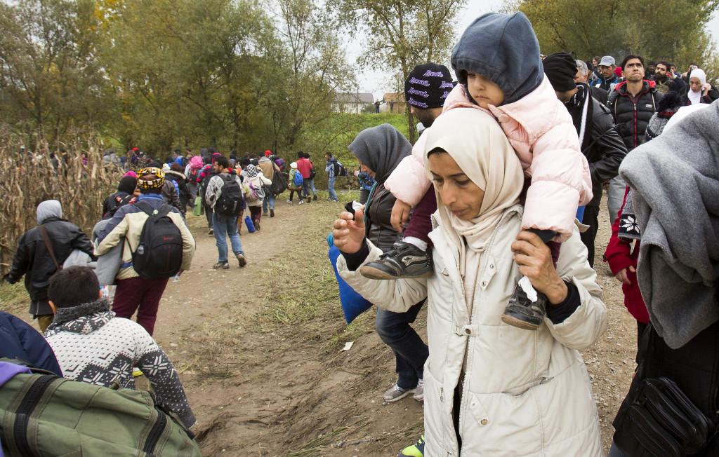 Människor på flykt får hjälp över gränsen mellan Kroatien och Slovenien. Kanske kommer några av dem till Sverige. Kommer de till respekt och trygghet eller till en osäker framtid? Foto: Darko Bendic/AP/TT