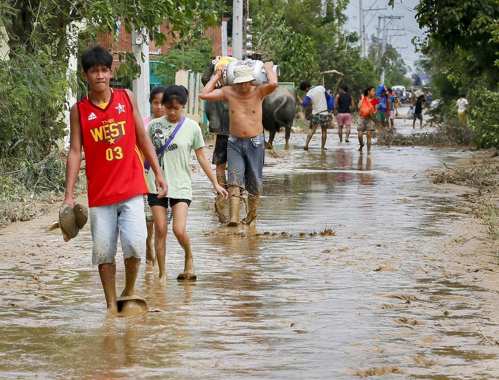 Tusentals människor på väg tillbaka till sina skadade hem efter tyfonen i Filippinerna i oktober. Foto: Bullit Marquez/AP/TT