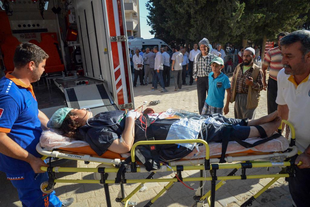 En kvinna som har blivit skadad i IS bombanfall i Kobane i Syrien får hjälp till sjukhuset. Foto: AP/TT