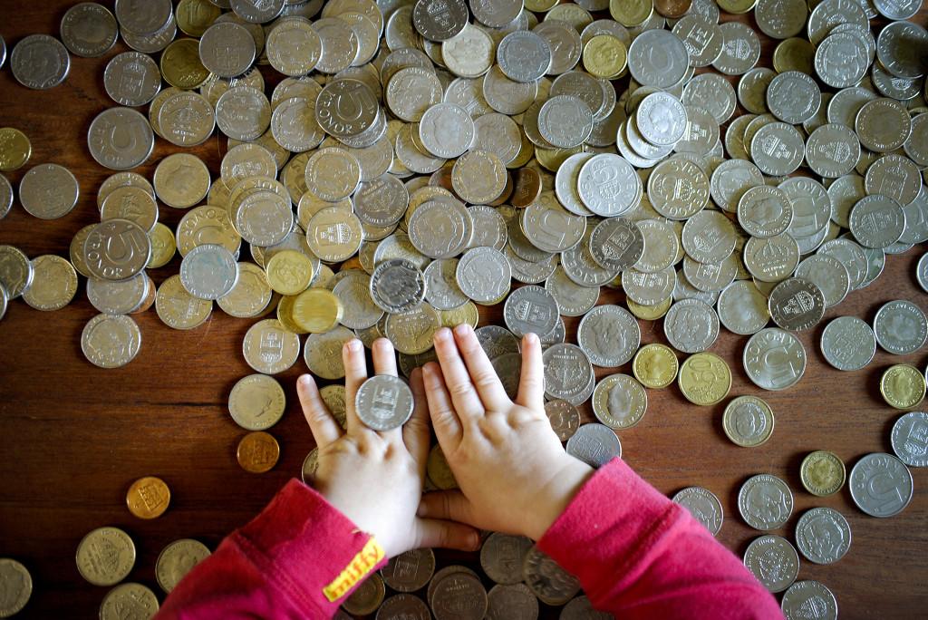 STOCKHOLM 20100831 : Ett barn leker med pengar, svenska mynt Foto: Jessica Gow / SCANPIX / Kod 10170