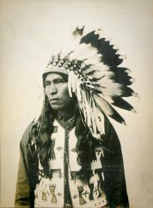 John Salda i Kanada fotograferades 1907 i traditionell huvudbonad. Troligtvis redan då ett uttryck för exotifieringen av hans folk. Foto: Byron Harmon/Public domain