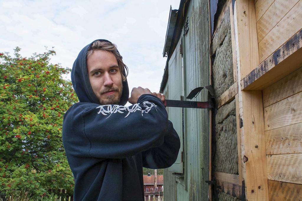 Julius Östberg bygger också sitt eget hem på hjul. Här tar han bort murkna brädor för att sätta dit nya. Foto: Carin Emenius
