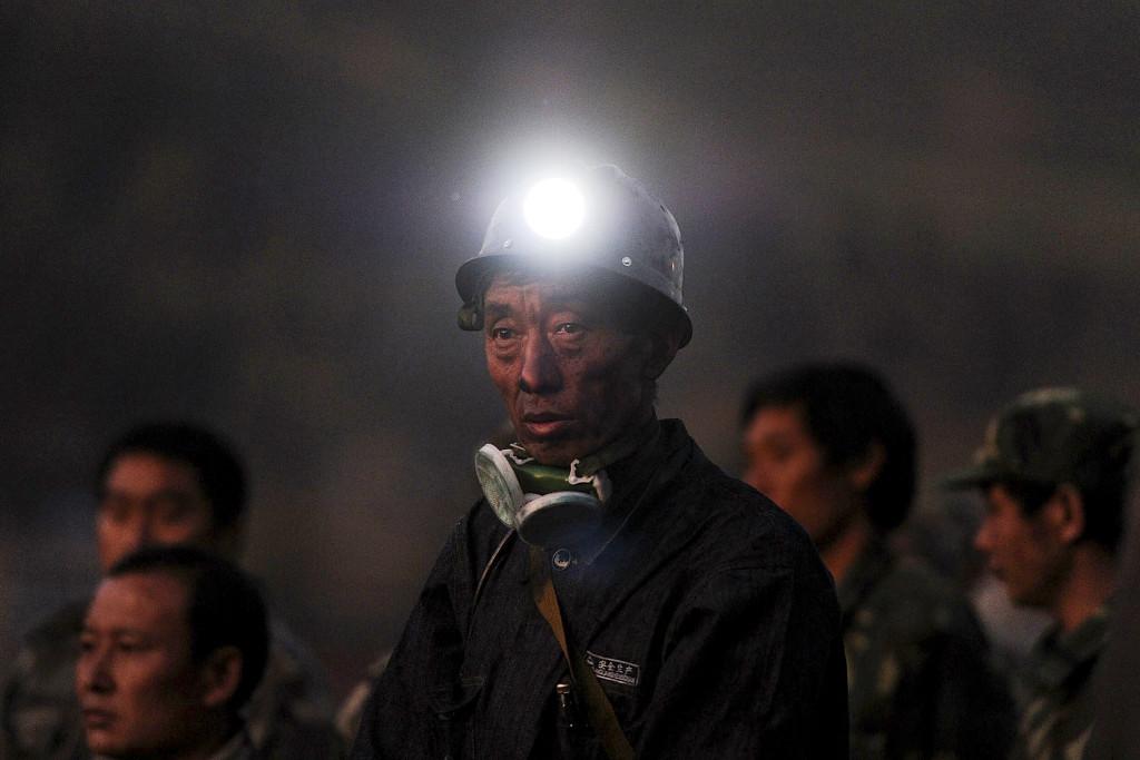 En gruvarbetare står och väntar på besked efter en gasolycka i Sizhuanggruvan, Kina, som dödade 20 och stängde in 23 personer 2011. Det ständiga osynliga hotet från den explosiva gasen i kolgruvorna får i Georges Didi-Hubermans bok symbolisera svårigheten att se katastrofen innan den inträffar. Foto: AP/TT