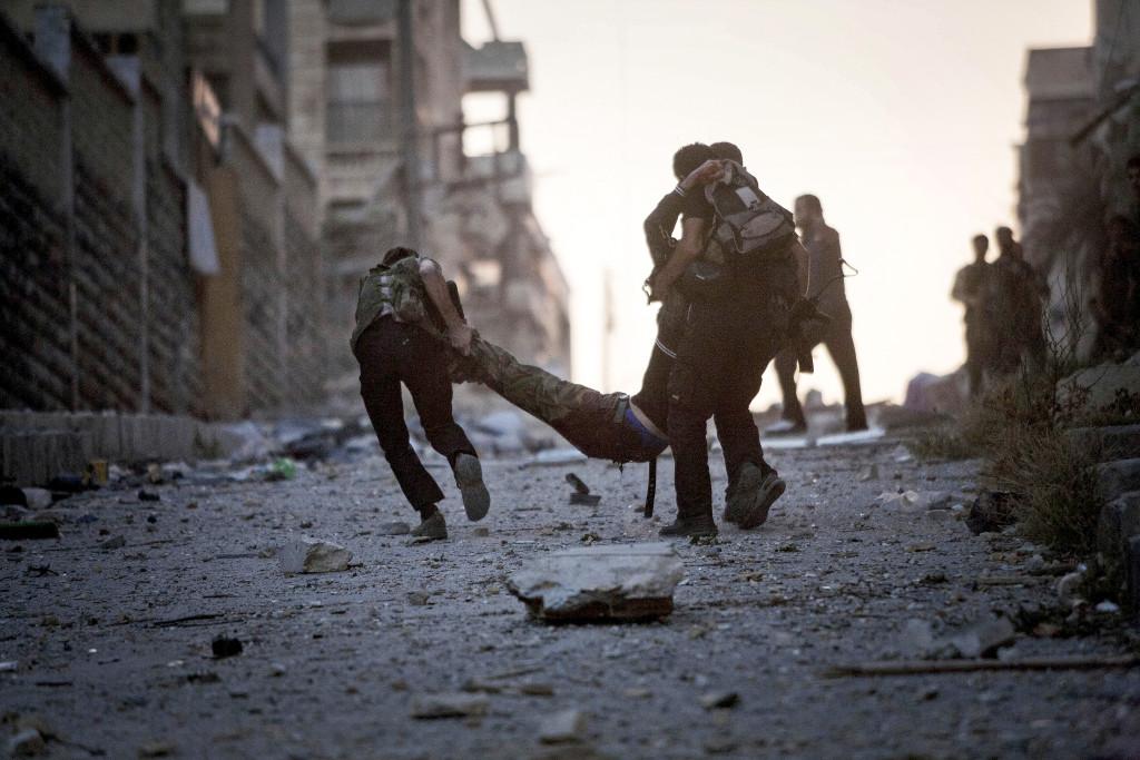 Soldater i FSA (Fria syriska armén) hjälper en allvarligt skadad kamrat, skjuten av en krypskytt från syriska armén i Aleppo. Foto: Manu Brabo/AP Photo/TT.