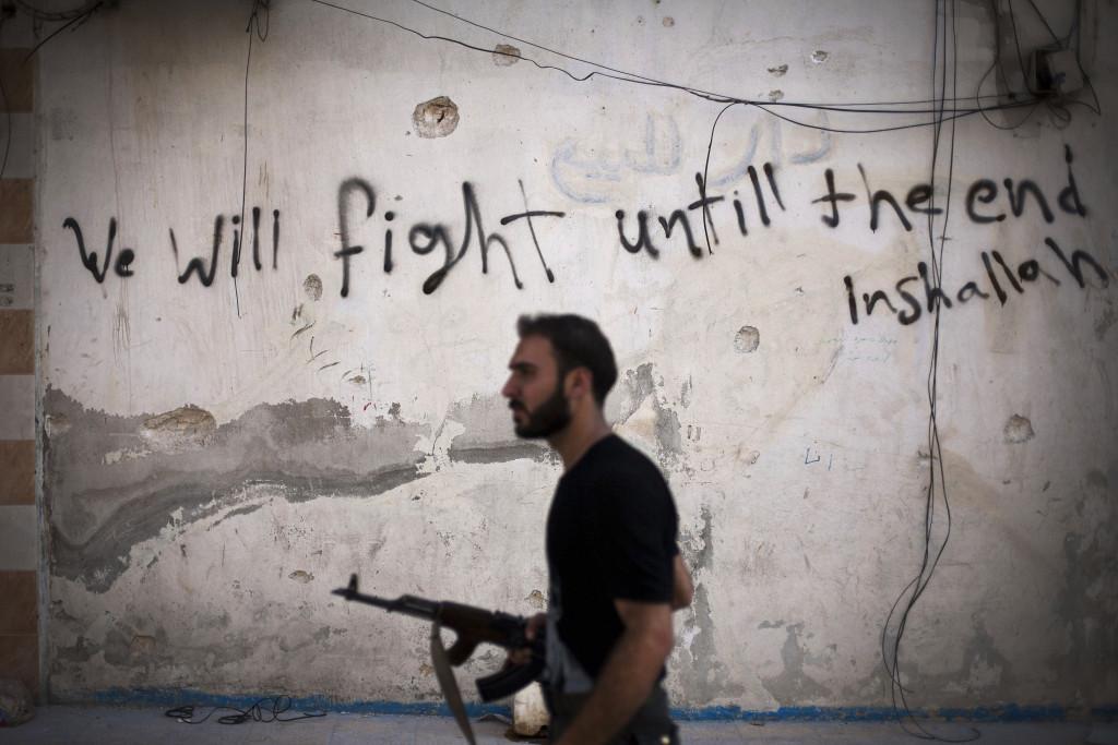 En FSA-soldat går genom Amariyadistriktet i Aleppo, september 2012. Foto: Manu Brabo/AP Photo/TT.