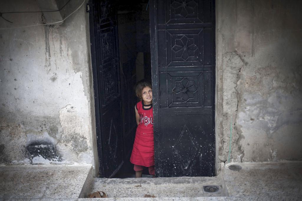 En syrisk flicka står i dörren till sitt hem där FSA och syriska armén strider i Amariyadistriktet i Aleppo, september 2012. Foto: AP Photo/ Manu Brabo/TT.