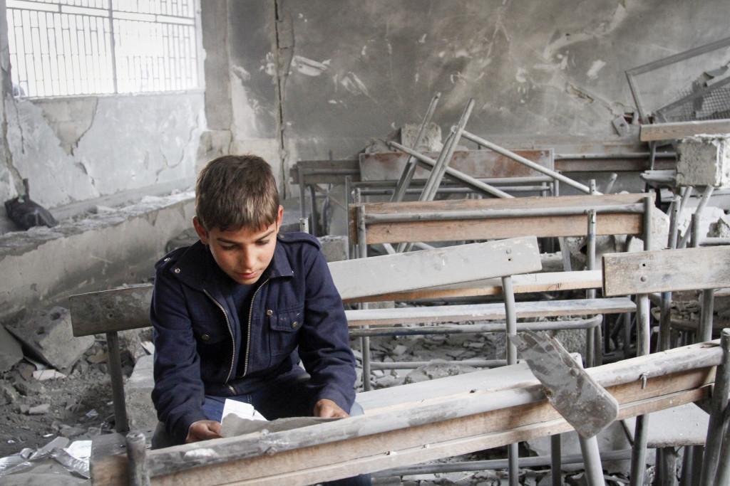 En syrisk pojke läser på ett trasigt papper i sitt gamla förstörda klassrum i Aleppo, november 2012. Foto: AP/TT.