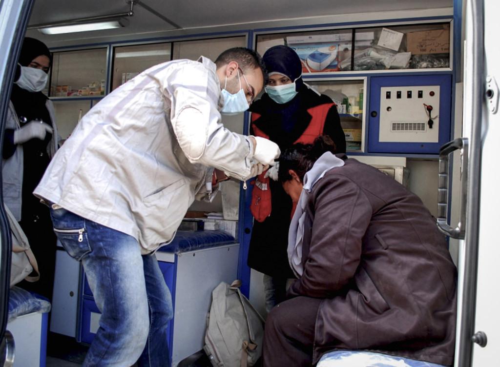 En skadad syrisk kvinna får vård i en ambulans efter att en bilbomb exploderat i byn al-Kaffat i Hamaprovinsen, januari 2013. Foto: AP Photo/SANA/TT.