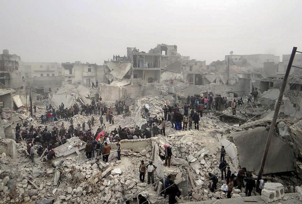 Denna bild tagen av en privatperson visar människor som söker igenom bråten från en byggnad sönderbombad av syriska statliga armén i Jabal Bedro-området i Aleppo februari 2013. Foto: Aleppo Media Center AMC/AP Photo/TT.