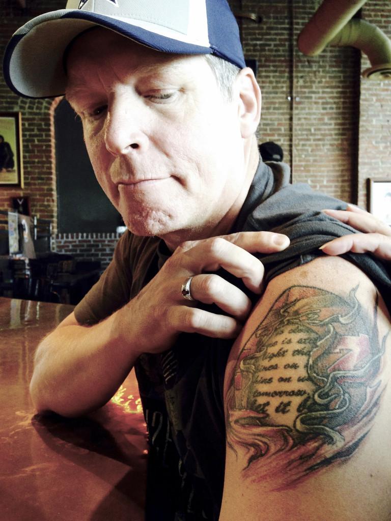 """Mike Reel hoppas se Donald Trump som USAs näste president eftersom han inte tycker att Republikanerna gått tillräckligt hårt åt """"kommunisten"""" Barack Obama. Mike visar sin tatuering med citat ur Beatles """"Let it be"""". Foto: Klas Lundström."""