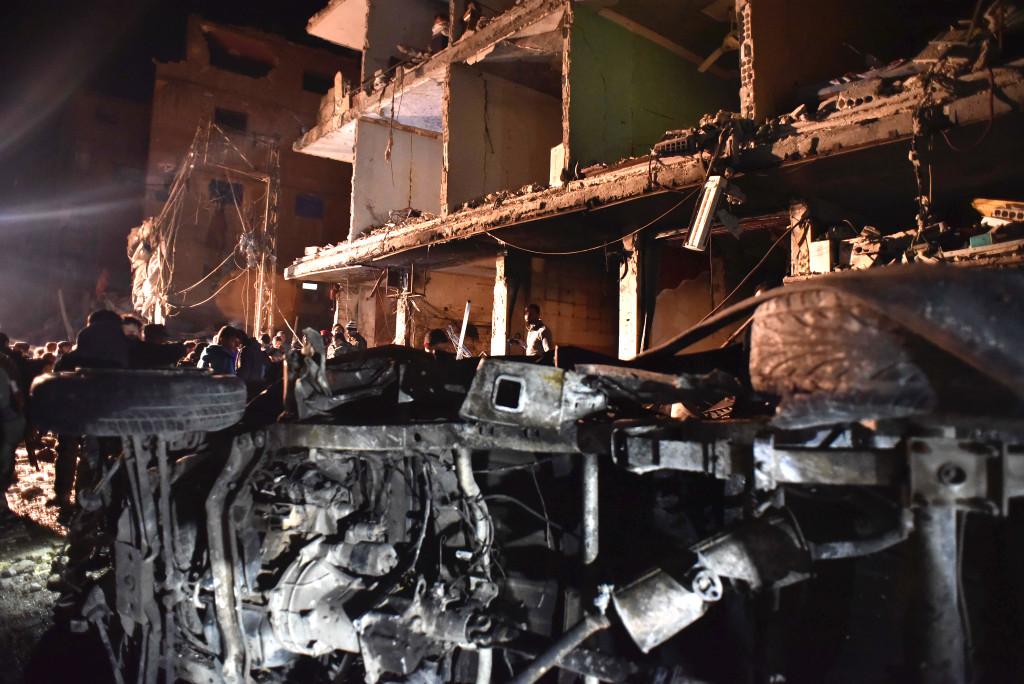 Folk samlas i förödelsen efter en bomdattack i Sayyida Zeinab, söder om Damaskus i Syrien. IS har tagit på sig trippelattacken som skedde i söndags. Över 100 människor dog. Foto: AP Photo/Natalia Sancha/TT.