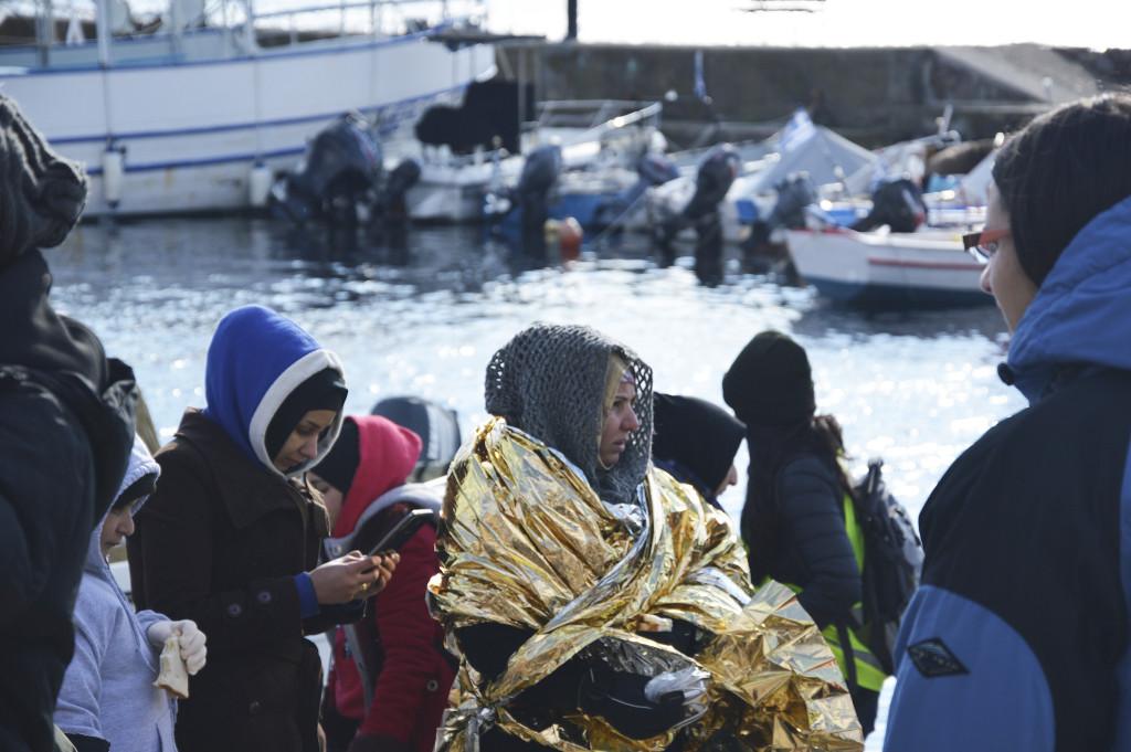 Ett trettiotal flyktingar anländer i Molivos hamn, de har plockats upp från en gummibåt av kustbevakningen. Volontärer kommer med torra kläder, vatten och smörgåsar.