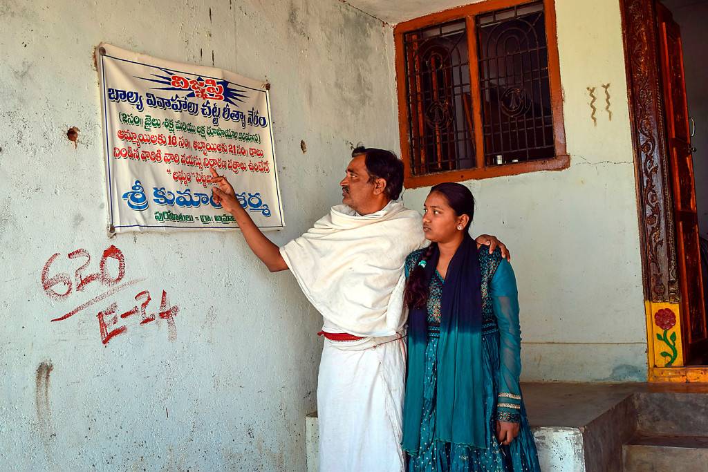 Den hinduiske prästen Shri Kumar Sharma visar tillsammans med sin dotter på den varning mot bortgifte av barn som sitter utanför hans kontor. Foto: Stella Paul/IPS.