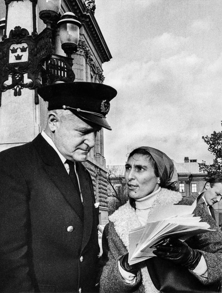 Året är 1967. Katarina Taikon delar ut flygblad framför riksdagshuset, men stoppas av vaktmästaren. Foto: John Kjellström/SvD/TT.
