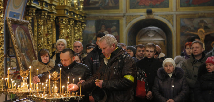 "Ukrainian Orthodox believers light candles during the memorial service for the Heavenly hundreds in the Mikhaylivsky Cathedral in Kiev, Ukraine, Saturday, Feb. 20 2016. The ""Heavenly Hundred"" is what Ukrainians in Kiev call those who died during months of anti-government protests in 2013-14. (AP Photo/Sergei Chuzavkov)"