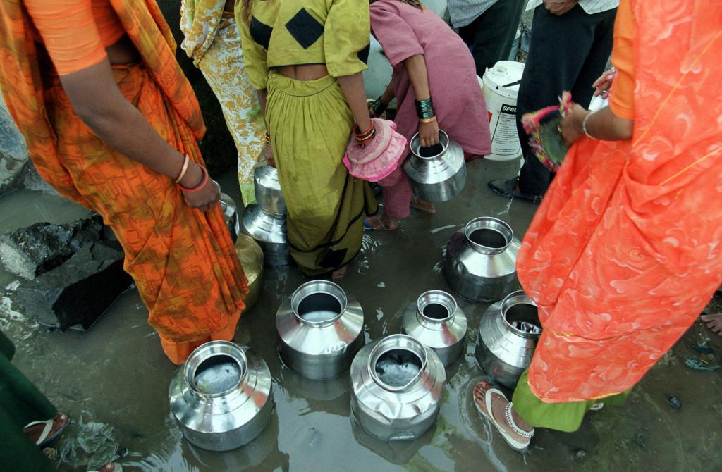 Kvinnor hämtar vatten i Rajkot, India. I denna by finns endast en vattenkran för alla människor i området. Foto: AP Photo/Manish Swarup/TT.